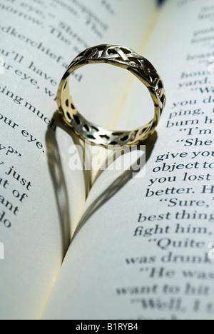 Ring mit herzförmigen Schatten auf ein offenes Buch liegend