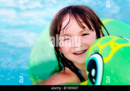 Nettes Lächeln auf den Lippen Kind Paddeln im Schwimmbad - Stockfoto