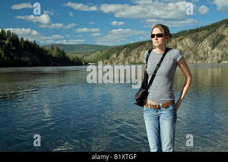 Frau mit Blick auf den Yukon und Klondike River in Dawson City, Yukon. - Stockfoto