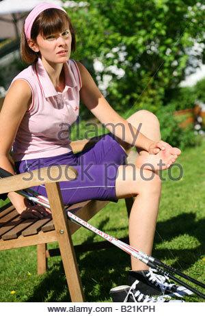 junge Frau, die ihre Füße untersuchen - Stockfoto