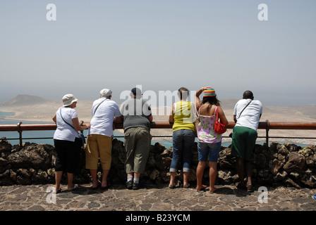 Eine Gruppe von Touristen genießen die spektakuläre Aussicht auf Isla De La Graciosa, vom Mirador del Rio auf Lanzarote. - Stockfoto