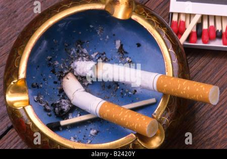 Zwei Zigaretten brennen in Aschenbecher - Stockfoto