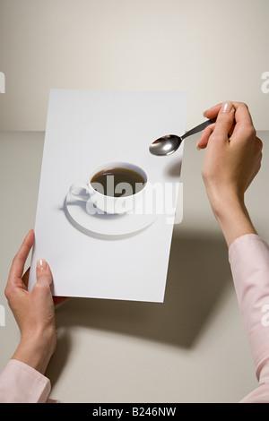 Eine Frau hält ein Foto von einer Kaffeetasse und einem Löffel - Stockfoto