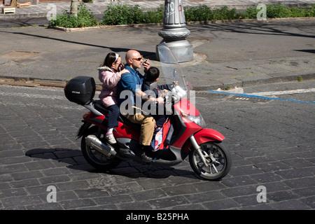 Mann fährt Motorrad mit seinen Kindern und Gespräche auf dem Handy in Catania, Sizilien, Italien - Stockfoto