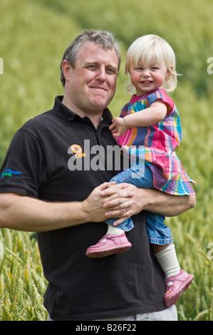 Ein stolzer Vater hält schützend seine Tochter mit beiden lächelnd an einem sonnigen Tag. - Stockfoto