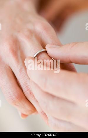 Putting Ehering am Finger Frau Mann - Stockfoto