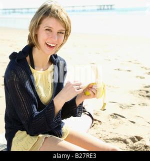 Frau Peeling Banane am Strand - Stockfoto