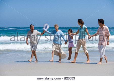 Familie aus drei Generationen zu Fuß am Strand, Hand in Hand - Stockfoto