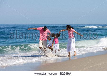 Vierköpfige Familie Wandern in Wellen am Strand - Stockfoto