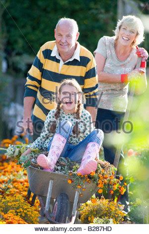Älteres paar Gartenarbeit, Enkelin (7-9) in Schubkarre, Porträt - Stockfoto
