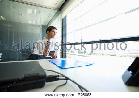 Geschäftsmann mit elektronischer Organizer in office - Stockfoto
