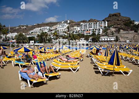 Menschen am Strand liegen mit Resort Ferienwohnungen auf Hügel Puerto Rico Gran Canaria Spanien - Stockfoto