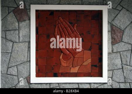 Skulptur von Palmen trat im Gebet wie in einen Bilderrahmen, ein Wandgemälde auf die Steinwand einer Kirche darzustellen Stockfoto