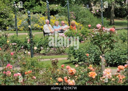 Menschen In den Park: Menschen im Park: Eine Gruppe älterer Menschen, die auf einer Bank sitzend bewundern die Rosengärten - Stockfoto