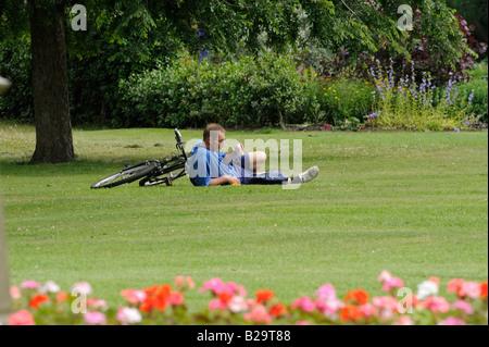 Menschen im Park: Ein müder Radfahrer nimmt eine Ruhe und trinken auf dem Rasen in Sheffield Botanical Gardens. - Stockfoto