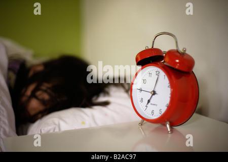 Mädchen im Alter von fünf schläft in ihrem Bett neben hellen roten Wecker Mixed Rennen indischen Englisch - Stockfoto