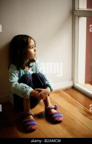 Porträt von kleinen Mädchen im Alter von fünf setzte sich auf den Boden neben Fenster Mischlinge indischen ethnischen - Stockfoto