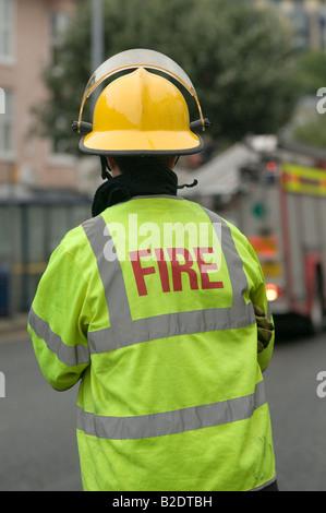 s Feuerwehr Offizier angesehen von hinten - tragen gelbe Helm und Sicherheitsweste für hohe Sichtbarkeit - Stockfoto
