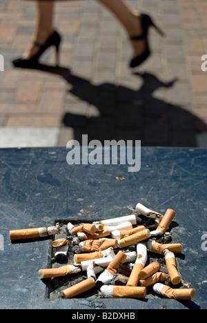 Zigarettenkippen auf einer britischen Straße Mülltonne mit einer Frau in Highheels vorbeigehen verworfen Stockfoto