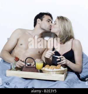 schöne junge caucasian Paar in einem Bett auf isolierte Hintergrund mit Frühstück im Bett - Stockfoto