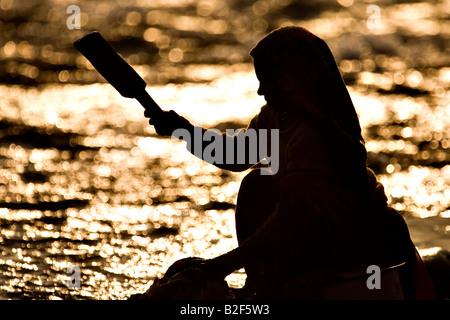 Silhouette einer indischen Frau, Waschen der Wäsche in einem Fluss bei surise - Stockfoto
