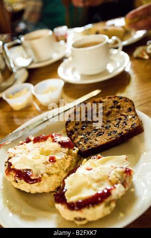 Englische Creme Tee mit Scones Marmelade und Clotted Cream und Obstkuchen in belebten Traditionscafé - Stockfoto
