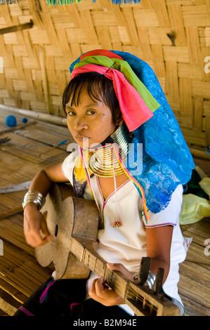 Eine bunte Padong Frau spielt ein traditionelles Saiteninstrument Musik Stockfoto