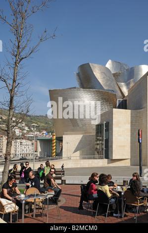 Junge Leute sitzen im Café im Freien Tische vor Museo Museum Guggenheim Kunst Galerie Bilbao Spanien - Stockfoto