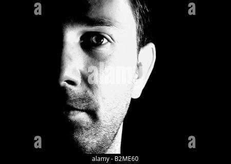 Eine krasse schwarz / weiss Portrait von einem kaukasischen Mann das Gesicht, halb im Schatten - Stockfoto