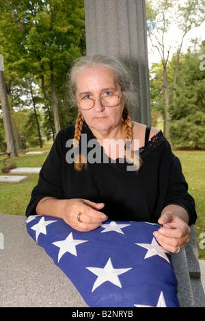 Frau, die Männer Ehering mit gefalteten amerikanische Flagge am Kriegerdenkmal Grab Granit - Stockfoto