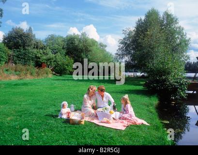 Familie von vier mit Sommer Picknick in der Nähe von See auf Wiese in Schweden - Stockfoto