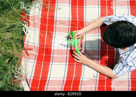 Jungen spielen mit grünen Spielzeug Flugzeug - Stockfoto
