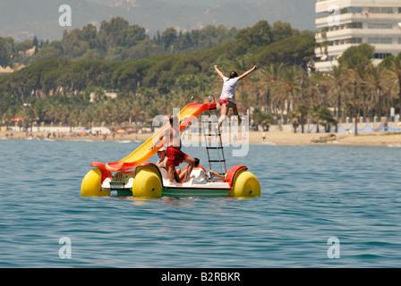Familie Spaß am Pedal Boot montiert mit Rutsche am Strand in Marbella - Stockfoto