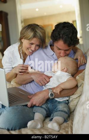 Junge Familie auf Sofa mit laptop - Stockfoto