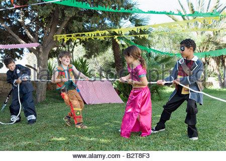 Kinder in Kostümen spielen Tauziehen - Stockfoto