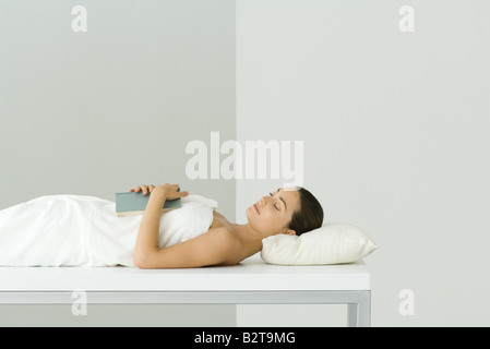 Frau liegend auf Massagetisch, Buch auf der Brust, Augen geschlossen hält. - Stockfoto