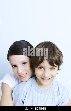 Schwester von hinten umarmt ihr Bruder lächelnd in die Kamera, Porträt - Stockfoto