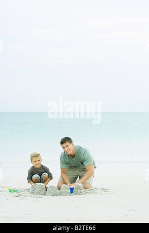 Vater und Sohn machen Sandburgen am Strand, in die Kamera Lächeln - Stockfoto