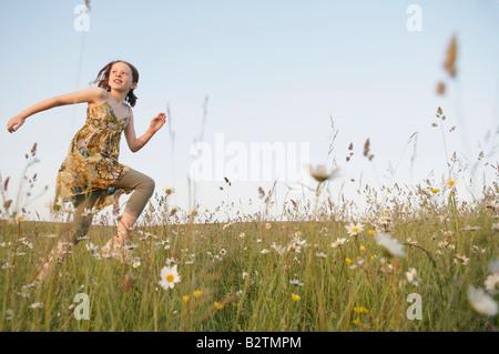 Mädchen läuft durch Feld, befasst sich mit Sonne - Stockfoto
