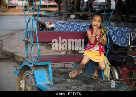 Ein junges Mädchen essen einen Snack auf der Straße in Luang Prabang in Laos. - Stockfoto