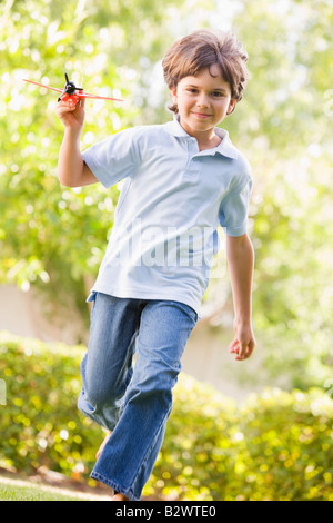 Junge mit Spielzeugflugzeug laufen im freien Lächeln - Stockfoto