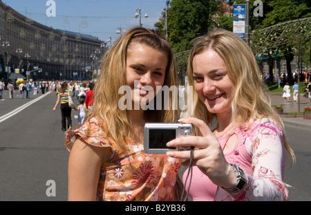 Zwei Mädchen im Teenageralter unter Selbstporträt mit Kamera in Straßenfest der Schließung der wichtigsten Straße - Stockfoto