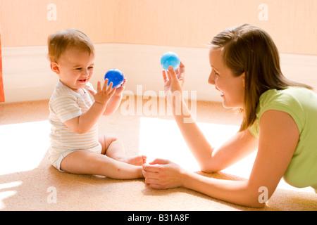 junge Mutter mit Baby mit kleinen Bällen zu spielen - Stockfoto
