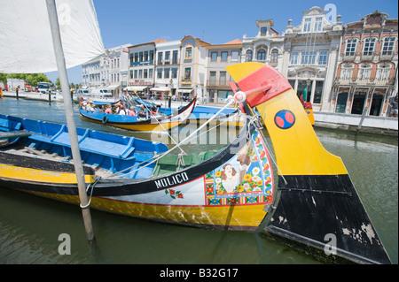 Traditionell bemalten Fischerboote in Aveiro, Portugal mit reich verzierten Gebäuden des alten Hafens im Hintergrund. - Stockfoto