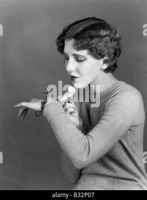 Frau mit Kosmetik-Etui am Handgelenk getragen - Stockfoto