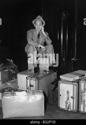 Mann, sitzend mit Gepäck - Stockfoto