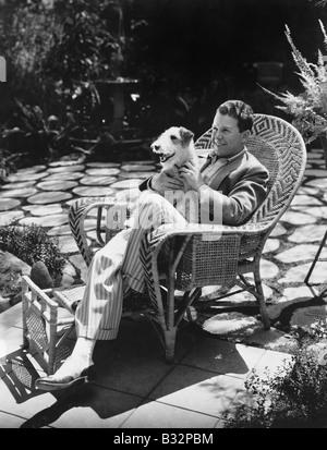 Mann sitzt im Stuhl außerhalb mit Hund - Stockfoto