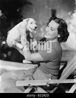 Junge Frau hält ihre Welpen und lächelnd - Stockfoto