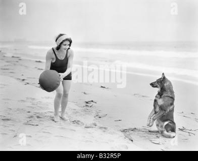 Junge Frau mit ihrem Hund und Ball spielen am Strand - Stockfoto