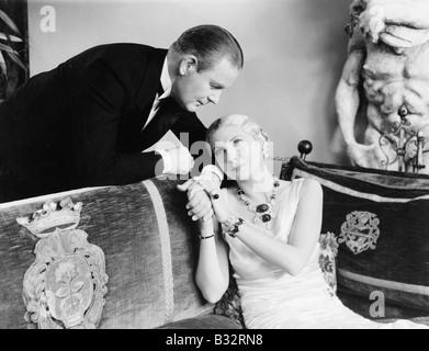 Junge Frau sitzt auf einer Couch und ein junger Mann Hand hält - Stockfoto